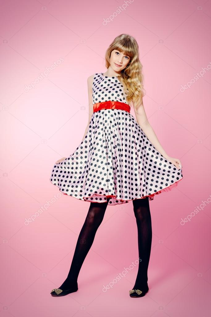 197d49326ff2 Full length portrait of a pretty teenager girl posing in pin-up dress over  pink background.