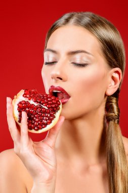 Attractive young woman eating fresh pomegranate. Sexual lips, red lipstick. Healthy food concept. Red background. stock vector