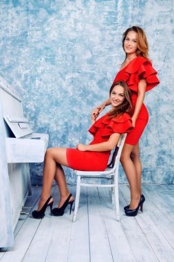 vintage romance. Beautiful twin sisters in evening red with piano.