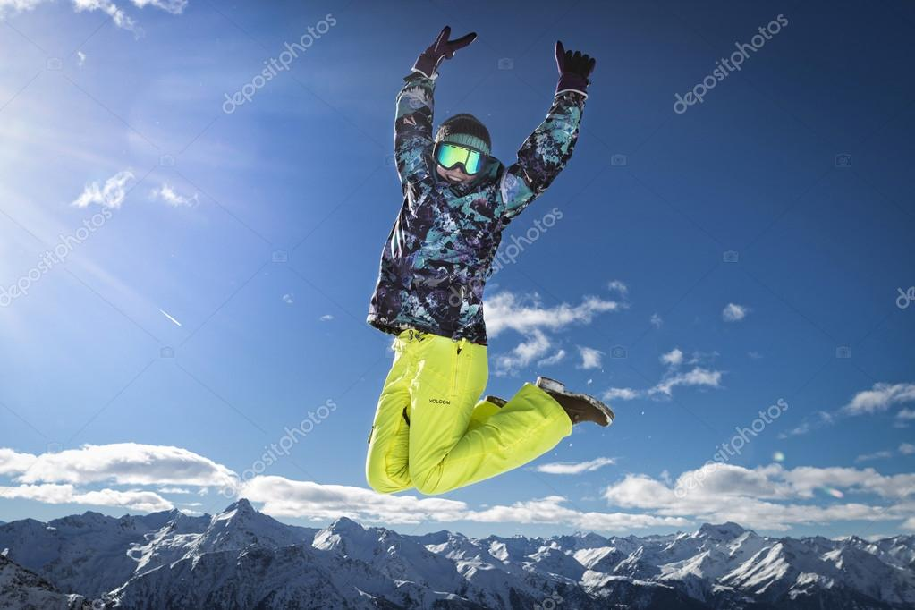 happy woman in ski clothes jumping over the snowy mounts in Austrian alps