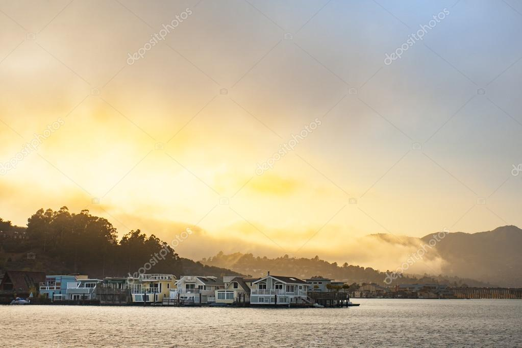 Golden sunset over the mountains, bay and coastal houses