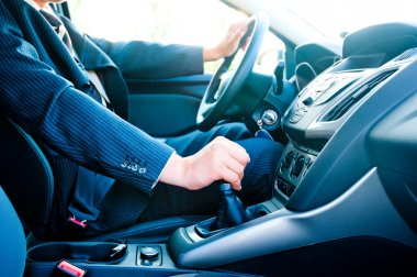 a man in a business suit in the car changes gear