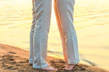 bare feet kissing couple at the sea