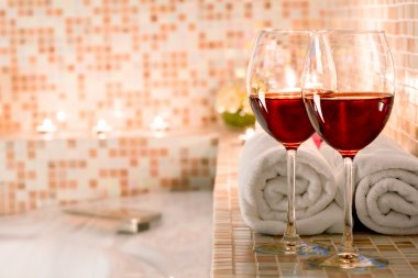 two glasses of wine and burning candles close-up in the bathroom