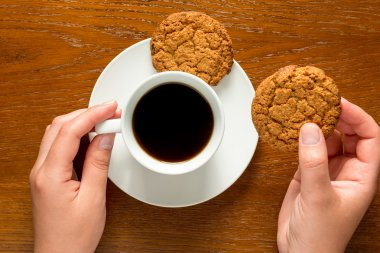 hands holding a cup of coffee and cookies top view