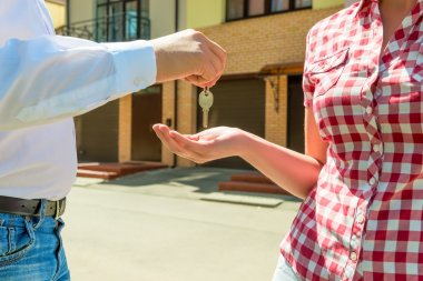 seller sends the house key new owner hands closeup