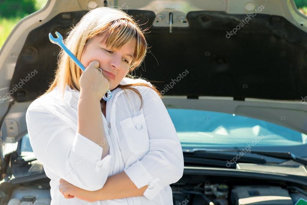 femme triste avec une cl pr s du capot ouvert d 39 une voiture photographie kosmos111 94037886. Black Bedroom Furniture Sets. Home Design Ideas