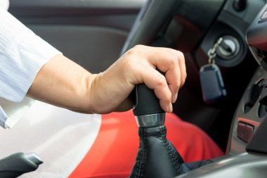 woman's hand holding a the shift lever in a car with manual tran