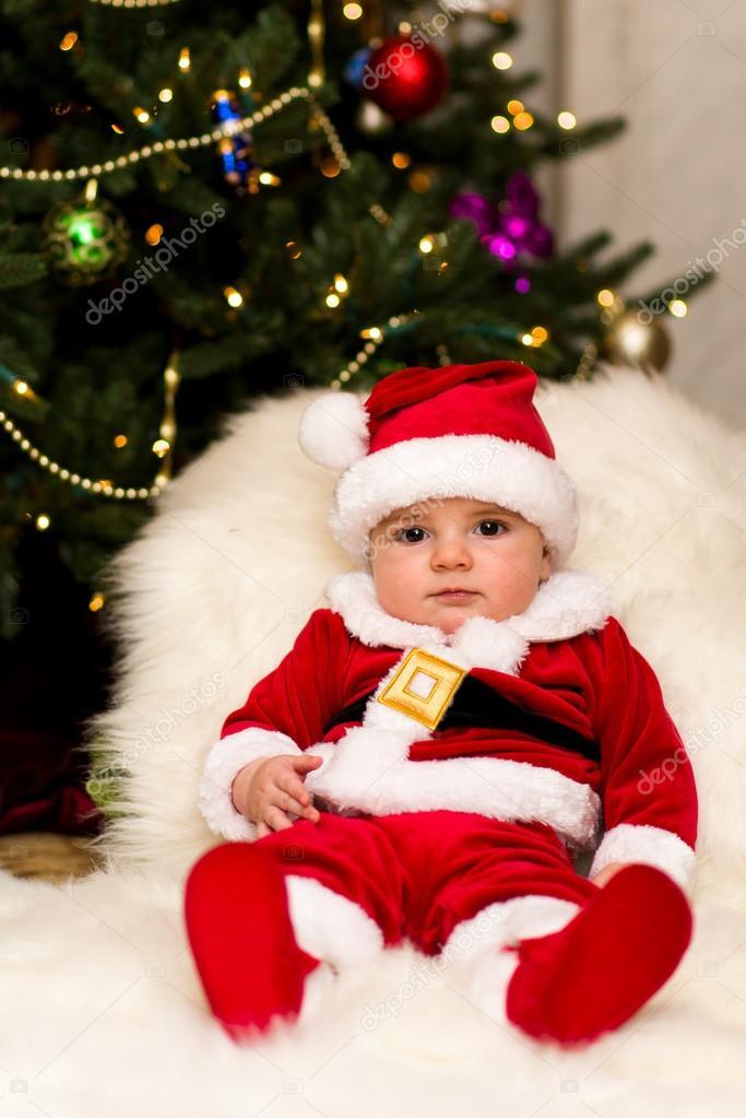 Un bambino vestito da Babbo Natale sotto l albero — Foto Stock ... 89931c800f9