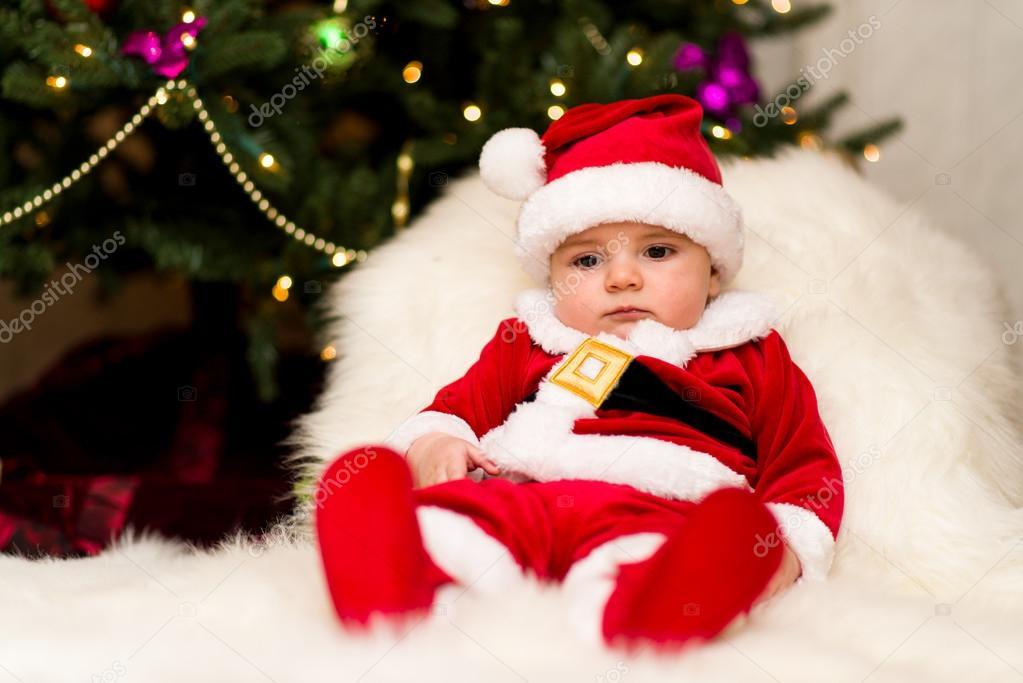 Un bambino vestito da Babbo Natale sotto l albero — Foto di Svyatkovsky db6cbc5248c
