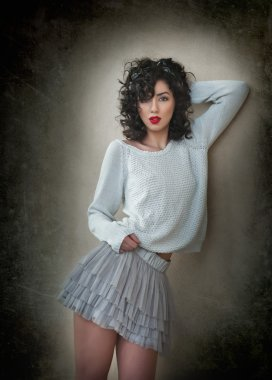 Charming young curly brunette woman in lace short skirt and white blouse leaning against wall. Sexy gorgeous young woman with long legs near wall. Portrait of sensual girl with voluptuous mouth posing