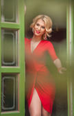 Fotografie Charming young blonde with red dress posing in a green painted door frame. Sensual gorgeous young woman in red outfit with Marilyn Monroe look, opening the door for somebody, exposing her leg