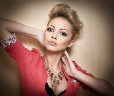 Hairstyle and Makeup, gorgeous female art portrait with beautiful eyes. Elegance. Genuine natural blonde with short hair in studio. Portrait of attractive woman with red blouse and glamorous necklace