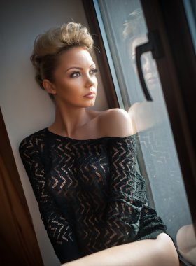 Attractive sexy blonde with black see through blouse looking on the window in daylight. Portrait of sensual short fair hair woman wearing low shoulder top, indoor scene. Beautiful woman daydreaming