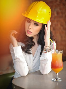 Beautiful woman civil engineer with yellow helmet taking a break in front of orange juice. Young female architect with white shirt drinking a juice in restaurant. Young female construction specialist