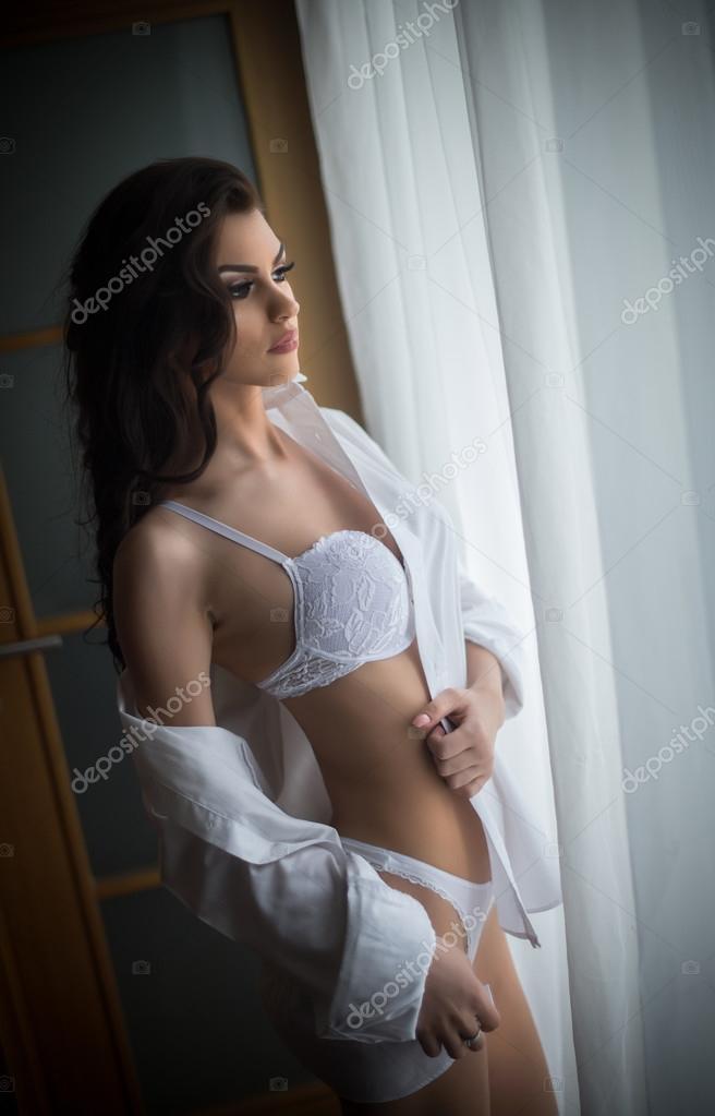 05b8ddbb1 Morena sexy atraente com lingerie de renda branca perto as cortinas olhando  na janela. Retrato de mulher de cabelos escuros sensual vestindo calcinha e  ...