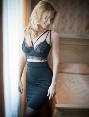 Attractive and sexy blonde woman with black lingerie and stockings posing staying near window curtains. Sensual female with fair hair posing smiling in luxurious scenery, boudoir concept