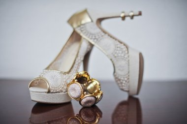 High heels wedding shoes and bracelet on table. Wedding accessories.
