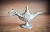 Fotografia lampada magica di Aladino antica. lampada genie dargento sul tavolo di legno. lampada ad olio vecchio stile