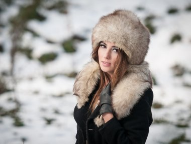 Portrait of young beautiful woman, outdoor shot in winter scenery. Sensual brunette girl with coat and fur cap posing in a park covered with snow. Fashionable female in a cold day.