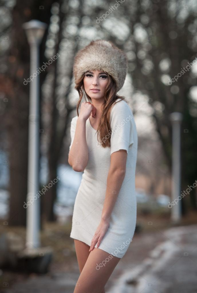 Portrait of young beautiful woman, outdoor shot in winter scenery. Sensual brunette girl in short white dress and fur cap posing in a park covered with snow. Fashionable female in a cold day