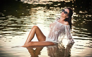 Young sexy brunette girl in wet white blouse posing provocatively in water. Sensual attractive woman with black sunglasses, summer shot. Long hair female with perfect body at beach during sunset.