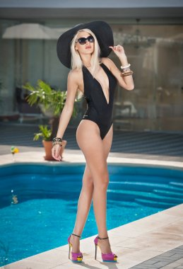 Beautiful sensual blonde with fashionable sunglasses and hat posing near a pool. Attractive woman in black low-cut swimsuit at swimming pool. Fair hair young female on high heels, summer shot.