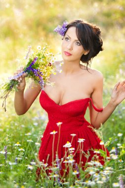 Young voluptuous brunette holding a wild flowers bouquet in a sunny day. Portrait of beautiful woman with low-cut red dress posing, outdoor shot. Provocative female enjoying the nature