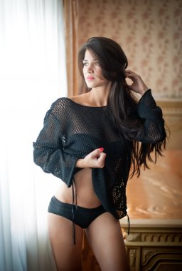 Young beautiful sexy woman in black blouse and panties posing in window light in vintage hotel room. Sensual brunette long hair female staying near a window. Attractive girl with transparent blouse