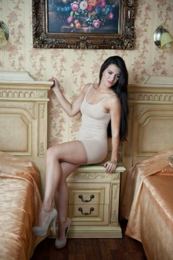 Young beautiful sexy woman in white short tight dress posing challenging indoor in vintage hotel room. Sensual brunette long hair female sitting provocatively on bedside furniture between hotel beds