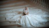 Fényképek Fiatal, gyönyörű luxus nő esküvői ruha félhomályban lépcsőház lépéseket ült. Menyasszony neki csokor gazdaság hatalmas esküvői ruha. Csábító szőke menyasszony a gyönyörű ruhát jelentő
