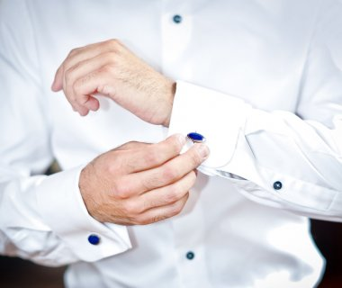 Man wears cuff-links on a shirt sleeve. A groom putting on cuff-links as he gets dressed in formal wear. Groom's suit