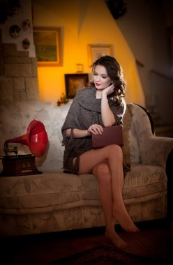 Beautiful young bare feet woman sitting on sofa holding a book having a red gramophone near her, vintage scenery. Attractive brunette girl with long hair and long legs sitting on couch posing smiling