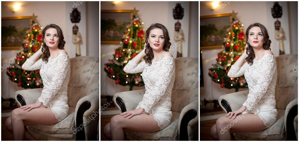 Beautiful sexy woman with Xmas tree in background sitting on elegant chair in cozy scenery. Portrait of girl posing pretty with short tight fit white dress. Attractive brunette female, indoor shot.
