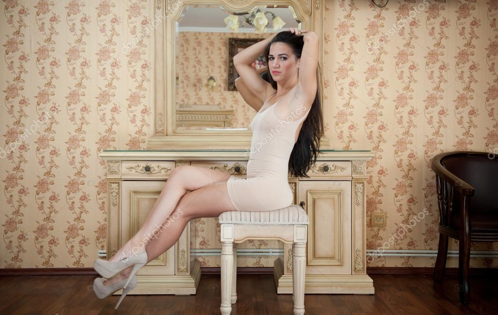 Charming Young Brunette Woman In Tight Fit Short Nude Dress Sitting On Chair Sexy -9939