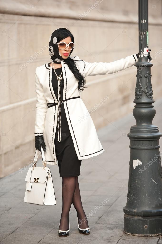 Attractive young woman in winter fashion shot. Beautiful fashionable young girl in black and white outfit posing on avenue. Elegant brunette with headscarf, sunglasses and handbag in urban scenery.