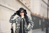 Téli divat vonzó fiatal nő lövés. Gyönyörű divatos fiatal lány fekete pózol a avenue. Elegáns barna, kalap, napszemüveg és kézitáska a városi táj.