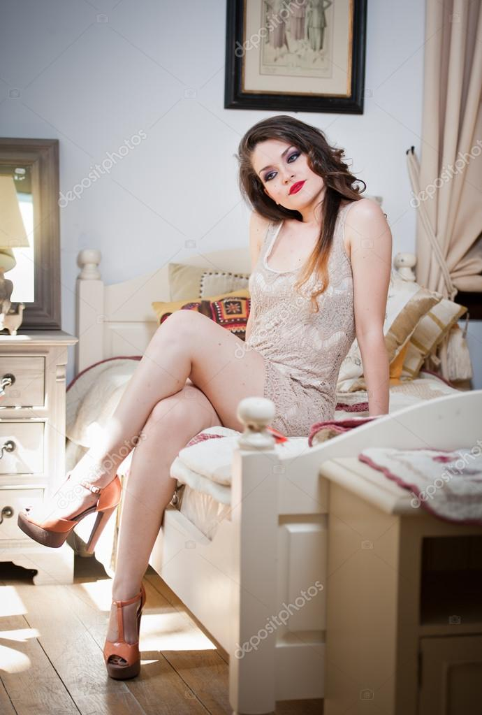 72818b0f5d9 Young beautiful sexy woman in white short tight dress posing challenging  indoor on vintage bed.