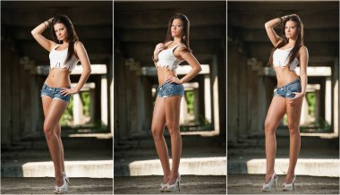 Portrait of a beautiful sexy woman with denim shorts and white cropped t-shirt in urban background. Attractive brunette posing provocatively in blue jeans on high heels. Young girl with long legs