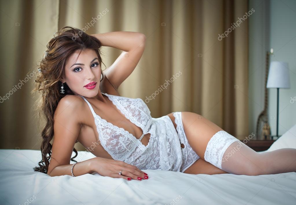 83b591bba61d7a Приваблива жінка в сексуальний білому білизна лежав у спокусливі позу на  ліжко. Брюнетка з сексуальний body.portrait сексуальна жінка позує в білому  білизна ...