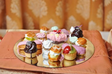 Wedding decoration with colored cupcakes, meringues and muffins. Elegant and luxurious event arrangement with colorful cakes. Wedding dessert. Set of tasty mini cakes on table