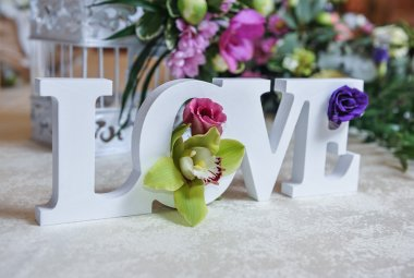 Wedding decor, LOVE letters and flowers on table. Fresh flowers and LOVE decoration on festive table. Luxurious wedding decoration on restaurant table. Elegant event