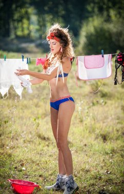 Sexy woman in lingerie with curlers in hair putting clothes to dry in sun. Sensual young female putting out the washing to dry in sunny day. Perfect body housewife, outdoors shot