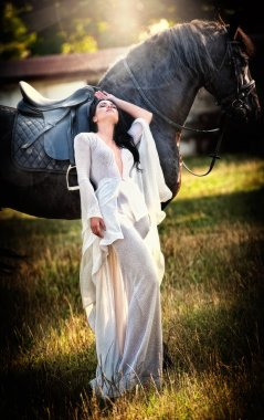 Fashionable lady with white bridal dress near brown horse in nature. Beautiful young woman in a long dress posing with a friendly black horse. Attractive elegant female with horse, sunny summer day