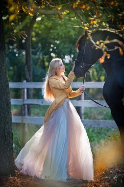 Fashionable lady with white bridal dress near black horse in forest. Beautiful young blonde woman in a long dress posing with a friendly horse. Attractive elegant female with horse, sunny summer day