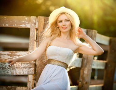 Beautiful blonde girl with country look near an old wooden fence in sunny summer day. Attractive woman with white hat and dress, American country style farmer. Long fair hair female in rustic style