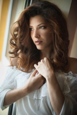 Attractive sexy brunette in white blouse posing provocatively in window frame. Portrait of sensual woman in classic boudoir scene. Woman with long hair daydreaming and enjoying the bright day light