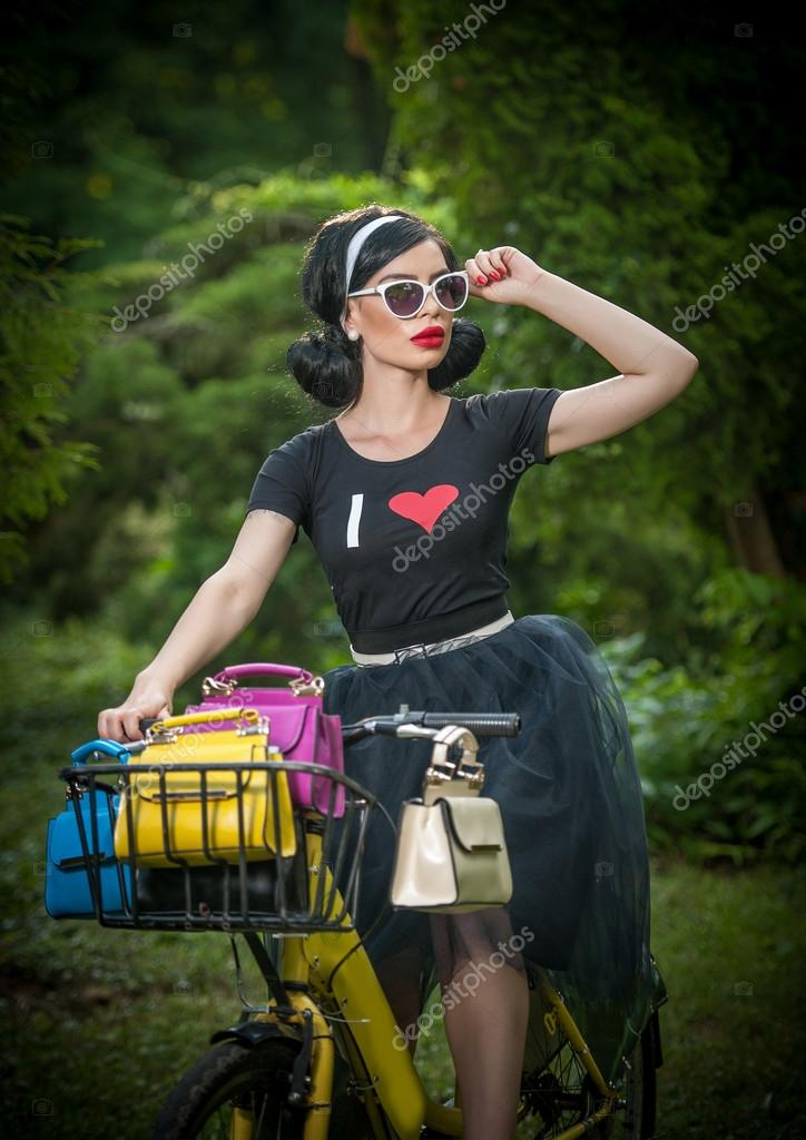 Beautiful girl with retro look wearing a black outfit having fun in park  with bicycle. 49596e2bb1f1