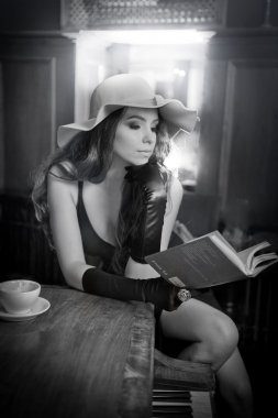 Young beautiful brunette woman with large romantic hat and gloves reading and drinking coffee near vintage piano. Sensual lady with long hair with a book in luxurious interior, black and white photo