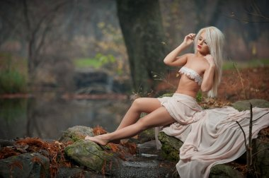 Lovely young lady sitting near river in enchanted woods. Sensual blonde with white clothes posing provocatively in autumnal park. Girl with fairy look in fall scenery. Romantic woman near lake